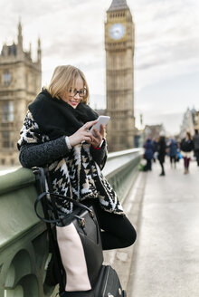 UK, London, young woman using her smartphone on Westminster Bridge - MGOF001545