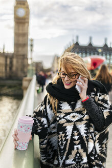UK, London, young woman talking on phone on Westminster Bridge - MGOF001548