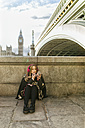 UK, London, young woman listening music and painting her lips near Westminster Bridge - MGOF001554