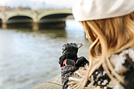 UK, London, young woman using her smartwatch near Westminster Bridge - MGOF001560