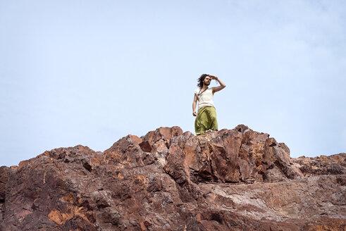 Man standing on rock shielding eyes - BMAF000105