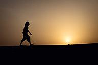 Silhouette of man walking on dune - BMAF000126