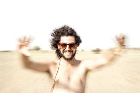 Bare chested man with sunglasses reaching out in desert - BMAF000147