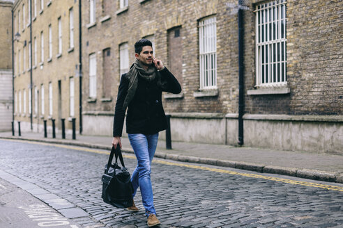 Young casual businessman walking in the street using mobile phone - BOYF000217