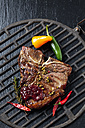 Porterhouse steak with chili peppers on grill - CSF027300