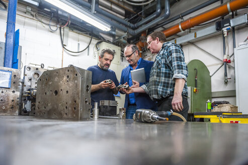 Three men in factory discussing workpieces - DIGF000046