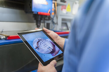 Man with digital tablet examining metal workpiece - DIGF000061