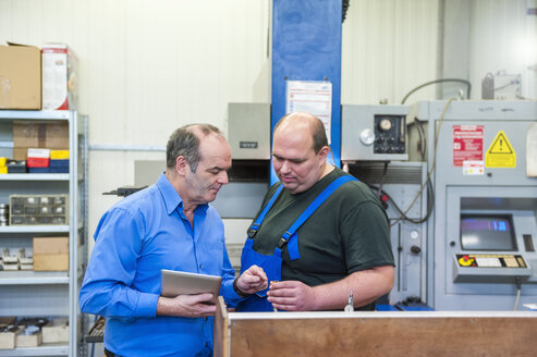 Two men in factory talking in a factory - DIGF000064