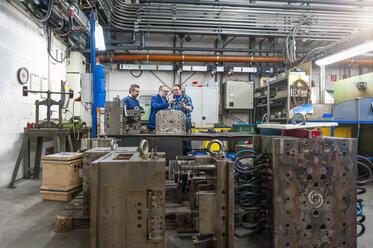 Three men in factory talking at metal workpiece - DIGF000085