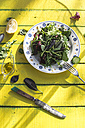 Spring salad of baby spinach, herbs, arugula and lettuce on plate, olive oil and lemon - DEGF000720