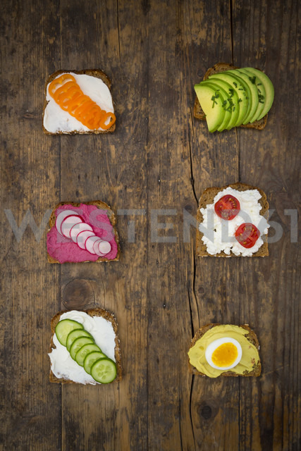 Wholemeal bread slices with different spreads and toppings on wood - LVF004664