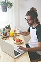 Young man using laptop while having breakfast - RTBF000016