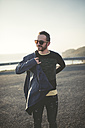 Portrait of smiling man with sunglasses putting on his jacket - RAEF000950