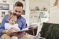 Father and little girl reading a book at home - MFF002882
