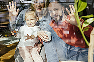 Mother, father and little girl waving out of window - MFF002894
