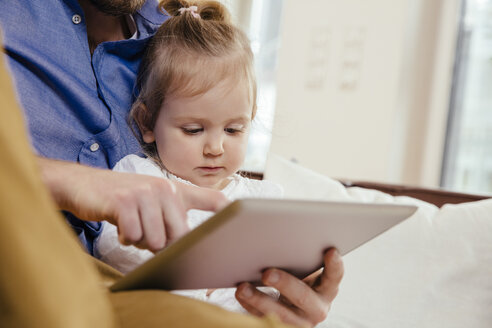 Father showing little daughter something on digital tablet - MFF002900