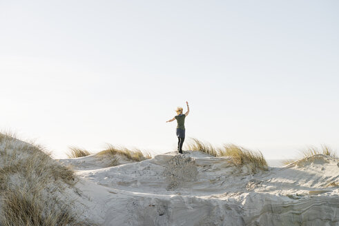 Denmark, Henne Strand, Happy woman standing on sand dune - BMA000183