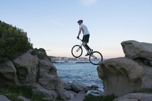 Bmx rider jumping from rock to to rock in the evening - SKCF000077