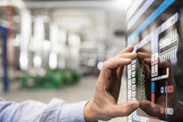 Man using touchscreen device in industrial plant - FKF001732