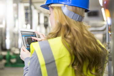 Woman wearing reflective vest controlling industrial plant with digital tablet - FKF001735