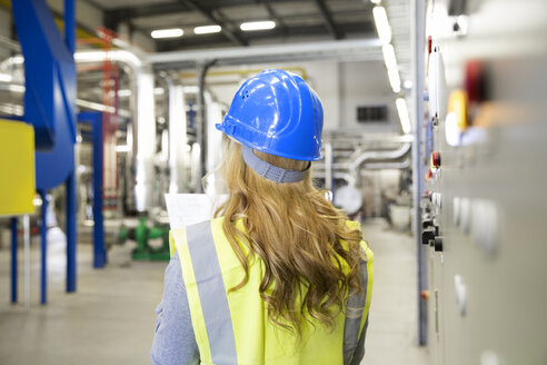 Woman wearing reflective vest controlling industrial plant - FKF001738