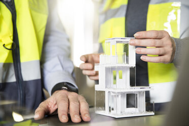 Close-up of colleagues wearing reflective vests with architectural model - FKF001741