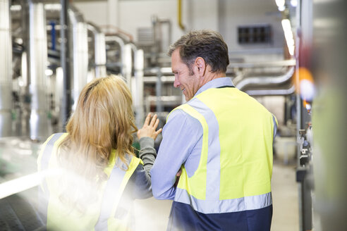 Colleagues wearing reflective vests talking in industrial plant - FKF001747