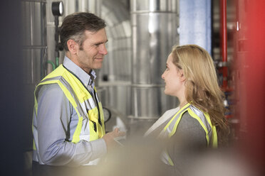 Smiling colleagues wearing reflective vests talking in industrial plant - FKF001750