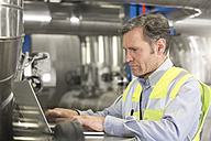 Man wearing reflective vest using laptop in industrial plant - FKF001753