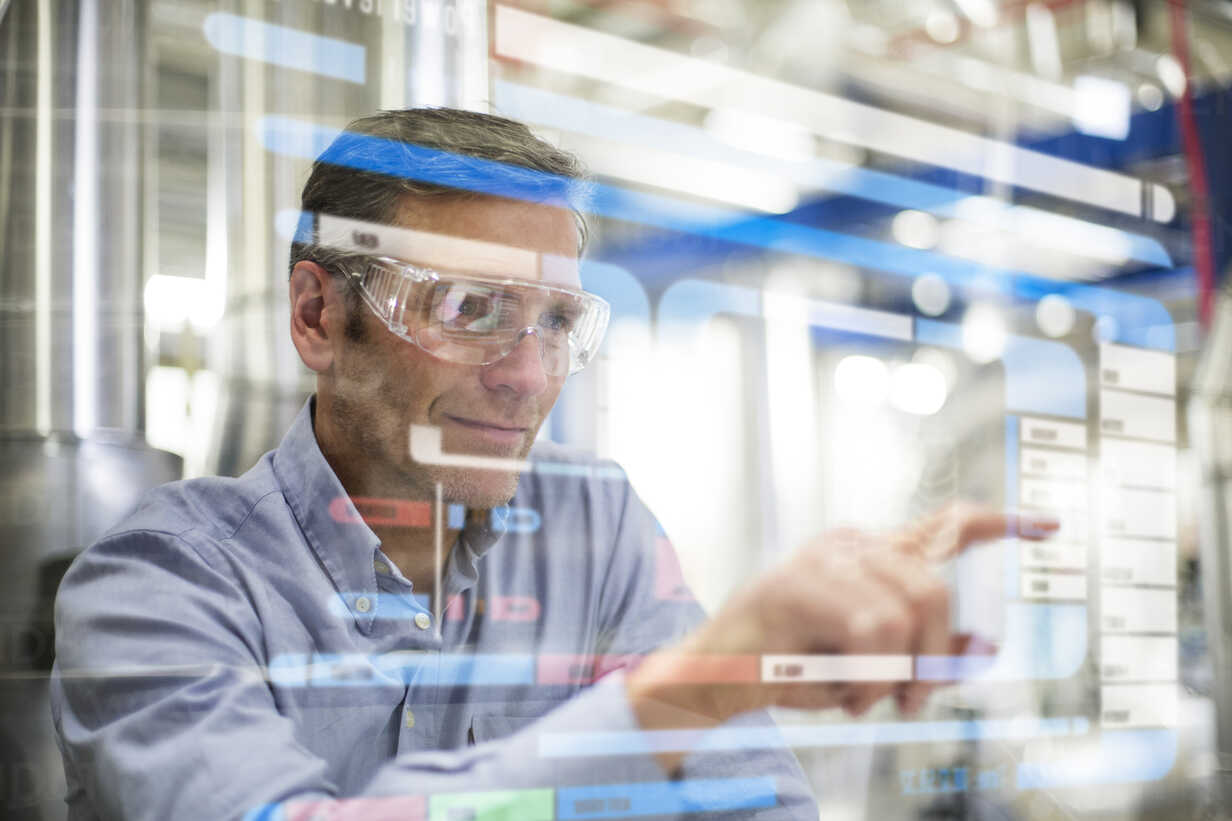 Man wearing safety goggles using transparent touchscreen device - FKF001759 - Florian Küttler/Westend61