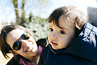 Portrait of baby boy with mother at the background watching him - GEMF000797
