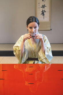 Portrait of woman wearing yukata drinking tea in a traditional Japanese room - GEMF000804