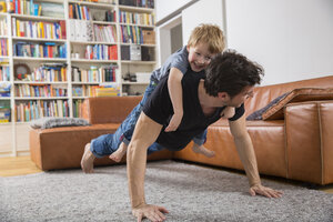 Father doing push ups in living room with son on his back - FMKF002527
