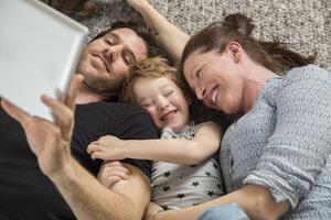Happy family lying on floor, using digital tablet - FMKF002581