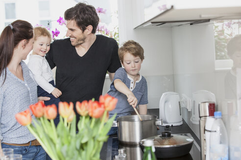 Family with two kids preparing food in kitchen - FMKF002590