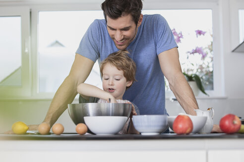 Father and son preparing waffle dough in kitchen - FMKF002596