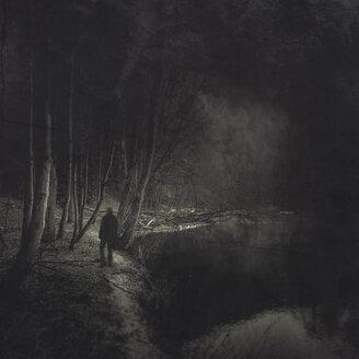Silhouette of man walking at riverside - DWI000711