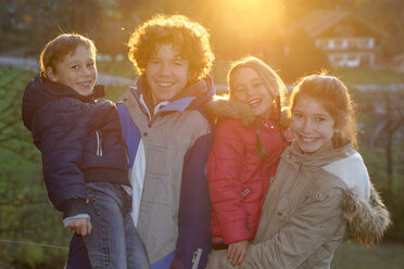 Group picture of four happy children and teenagers at backlight - LBF001421