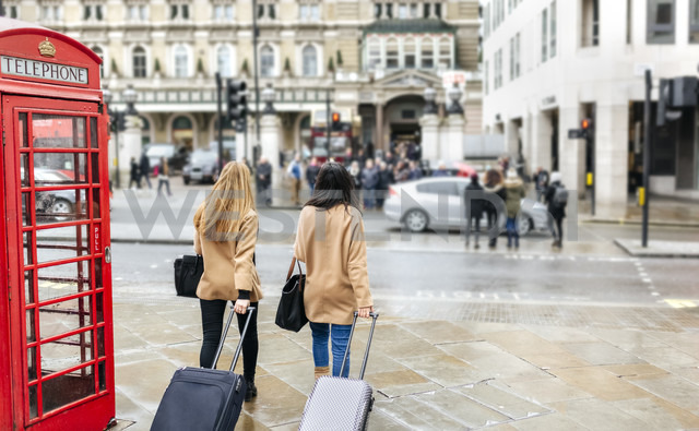UK, London, Two friends exploring the city, arriving with trolley bags - MGO001564