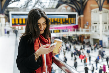 UK, London, Young woman using mobile phone at train station - MGO001570