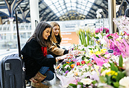 UK, London, Two young women admiring flowers at train station - MGOF001573