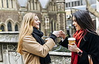 UK, London, Two friends exploring the city, drinking coffee in front of Southwark Cathedral - MGOF001576