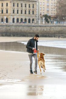 Spain, Gijon, man playing on the beach with his dog - MGOF001594