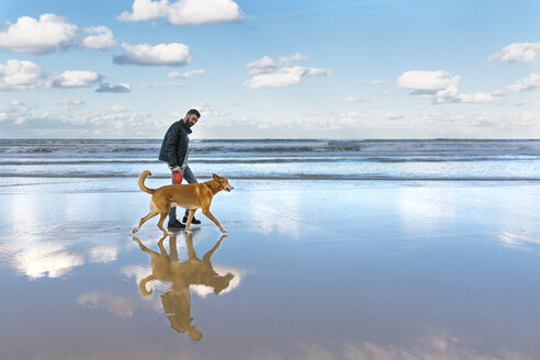 Man walking on the beach with his dog - MGOF001600