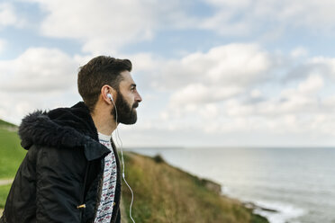 Profile of bearded man listening music with earphones looking at the sea - MGOF001606