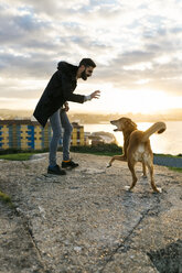 Spain, Gijon, man playing with his dog in the evening - MGOF001618