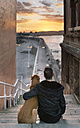 Spain, Gijon, back view of man and  his dog sitting on stairs watching sunset - MGOF001624