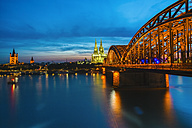 Germany, Cologne, view to lighted Cologne Cathedral with Hohenzollern Bridge in the foreground - TAMF000418