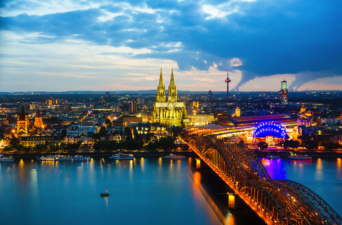 Germany, Cologne, view to lighted cityscape with Cologne Cathedral and Hohenzollern Bridge - TAMF000421