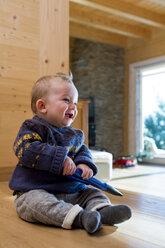 Baby boy sitting on wooden floor at home - ZOCF000005